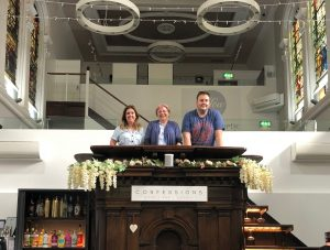 Three people stand in the former pulpit of The Trinity